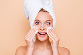 Portrait of glad cheerful positive model with turban on head after shower using two white cotton pads applying lotion on cheek isolated on beige background