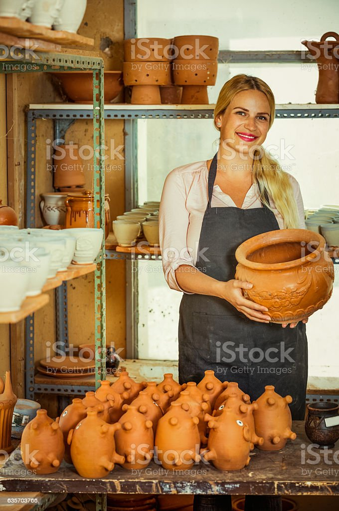 Portrait of glad woman pottery worker with ceramic crockery royalty-free stock photo