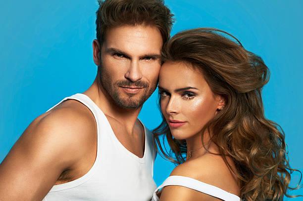 Portrait of glamour couple isolated on blue background stock photo