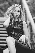 Portrait of curly woman in black dress sitting on a street