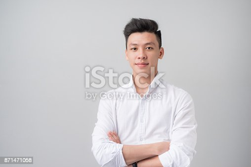 istock Portrait of good looking asian man over gray background. 871471058