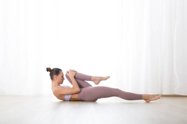 Porträt von wunderschönen aktiven sportlichen jungen Frau üben Yoga im Studio. Schöne Mädchen Praxis Pavana Muktasana, Wind entfernen Yoga Pose. Gesunder aktiver Lebensstil, Training drinnen im Fitnessstudio – Foto