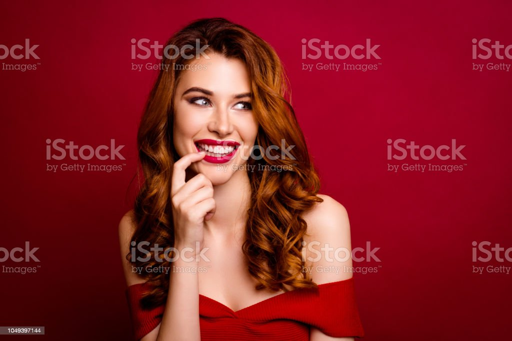 58ee7e6b540a Portrait of gorgeous, good-looking, alluring woman with modern curly  hairstyle look aside holds a finger near the lips isolated on dark red  background ...