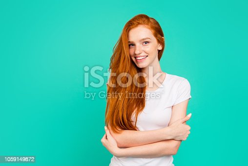 Portrait of gorgeous, nice, stunning, adorable, good-looking young girl in white polo with long hair hug herself and smile, stand isolated on pastel teal background with copy space for text