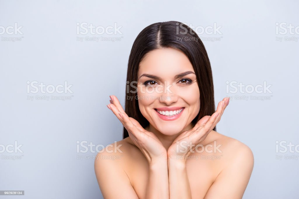 Portrait of gorgeous toothy woman presenting perfect smooth soft idyllic face skin isolated on grey background. Detox botox collagen vitamins minerals wellness wellbeing enhancement concept stock photo