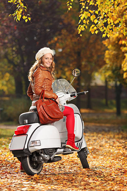 Portrait of gorgeous young woman on scooter in the park Portrait of gorgeous young woman on scooter posing in the park female biker resting stock pictures, royalty-free photos & images