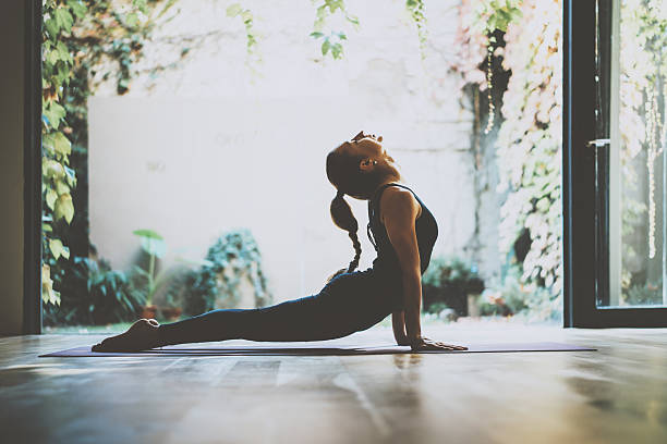 portrait of gorgeous young woman practicing yoga indoor. beautiful girl - vitality stock photos and pictures