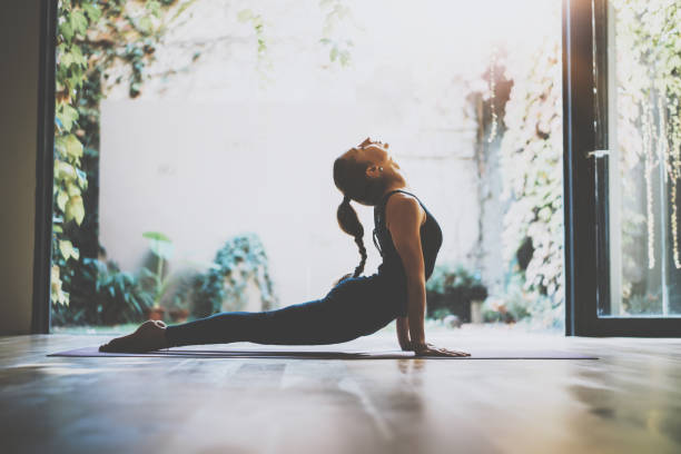 portrait of gorgeous young woman practicing yoga indoor. beautiful girl practice cobra asana in class.calmness and relax, female happiness.horizontal, blurred background.visual effects. - yoga stock photos and pictures