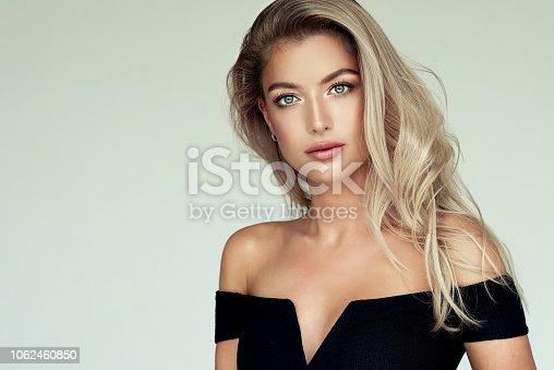 Young golden haired pretty model tenderly looking ot viewers. Portrait of gorgeous young woman with elegant make up and freely lying colored hairstyle. Hair coloration, hair care and cosmetology.