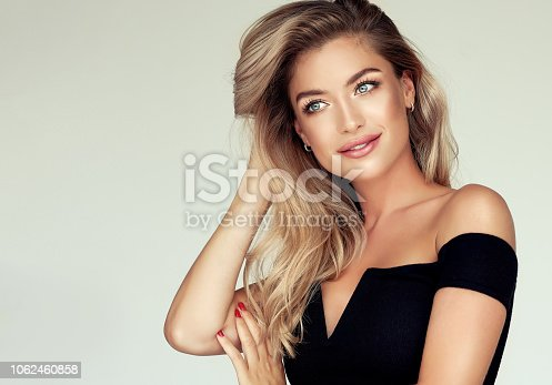 Young golden haired pretty model tenderly looking aside with light smile and touching  well groomed hair. Portrait of gorgeous young woman with elegant make up and freely lying colored hairstyle. Hair coloration, hair care and cosmetology.