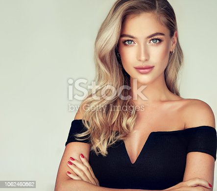 Young golden haired pretty model tenderly looking ot viewers with light smile. Portrait of gorgeous young woman with elegant make up and freely lying colored hairstyle. Hair coloration, hair care and cosmetology.