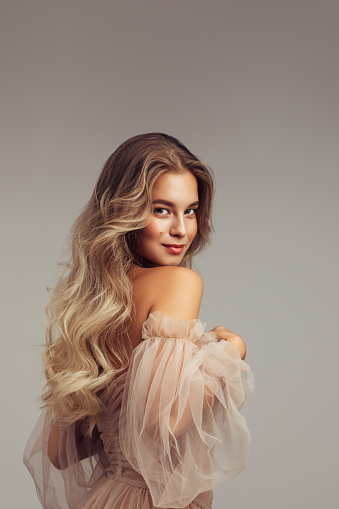 Portrait of gorgeous young woman with elegant make up and perfect golden hairstyle