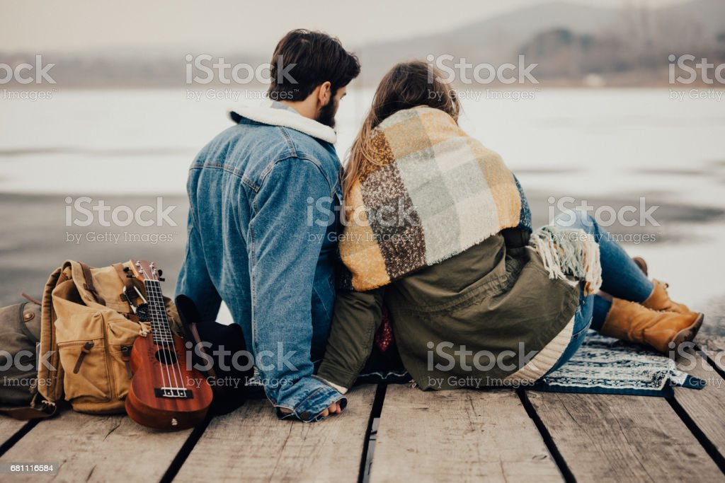 Portrait of gorgeus couple sitting on the pier and gazing into frozen water royalty-free stock photo