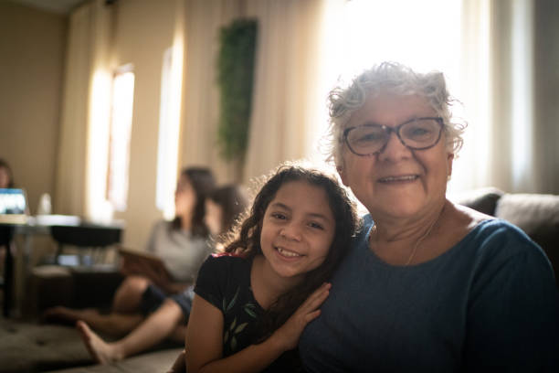 Portrait of grandmother and granddaughter at home stock photo
