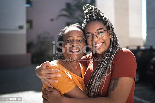istock Portrait of grandmother and granddaughter embracing outside 1251565479