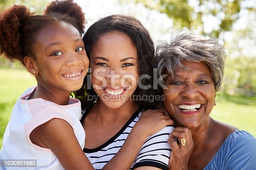 Portrait Of Grandmother With Adult Daughter And Granddaughter Relaxing In Park