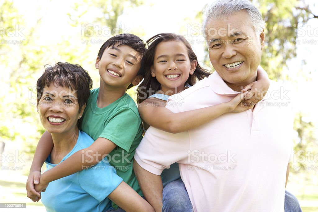 Portrait Of Grandparents With Grandchildren In Park stock photo