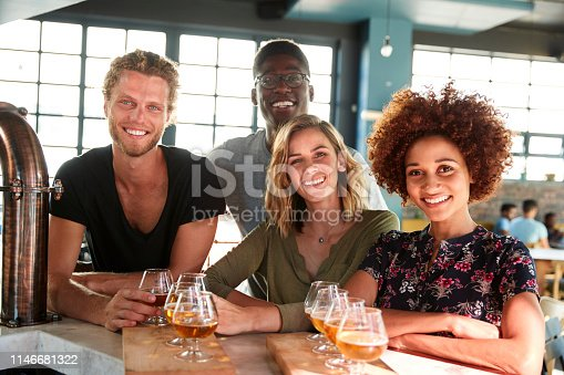 Portrait Of Group Of Friends Beer Tasting Sitting At Bar