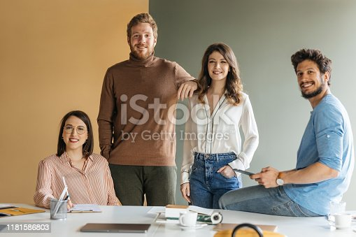 Portrait of group of modern smiling businessmen and businesswomen at office looking at camera.