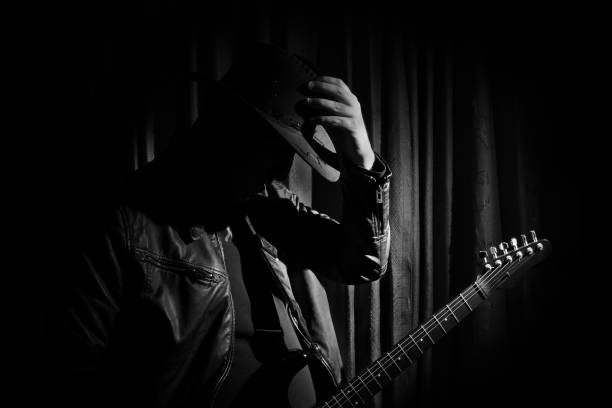 portrait of Guitarist Silhouette of guitar player. Portrait of guitarist . Music concept, guitarist in dark. Black and white photo. country and western music stock pictures, royalty-free photos & images
