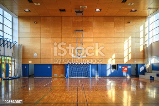 Wide angle view of empty gym with parquet basketball court and natural light coming through windows.