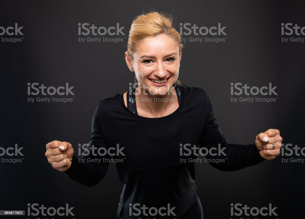 Portrait of gym female trainer making winner gesture royalty-free stock photo