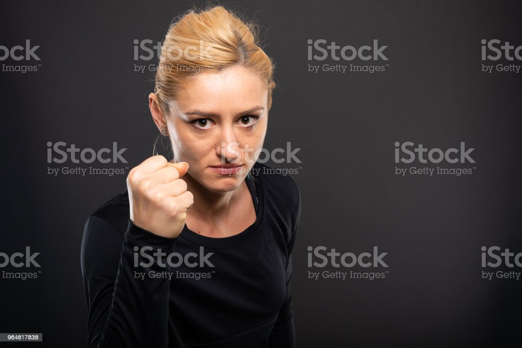 Portrait of gym female trainer showing fist royalty-free stock photo