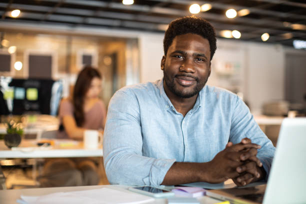 Portrait of Haitian male entrepreneur in co-working space Portrait of handsome Haitian man at work, sitting at desk and looking at camera, smiling haitian ethnicity stock pictures, royalty-free photos & images