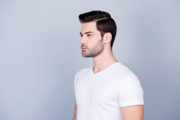 portrait der hälfte wandte sich atemberaubende mann im weißen t-shirt mit modernen frisur weiche glatte haut, isoliert auf grauem hintergrund - männerfrisuren stock-fotos und bilder