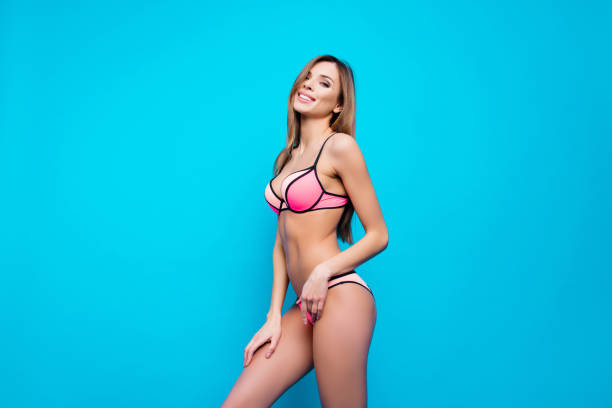 Portrait of half turned tempting sensual girl in swim wear posing having fit perfect body standing over blue background looking at camera Portrait of half turned tempting sensual girl in swim wear posing having fit perfect body standing over blue background looking at camera hot sexy butts stock pictures, royalty-free photos & images