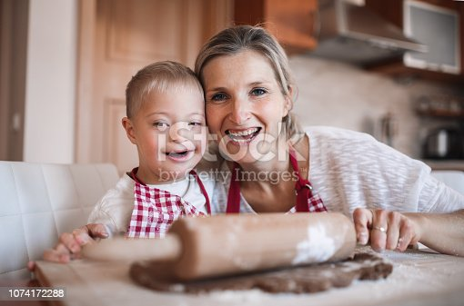 istock A portrait of handicapped down syndrome boy with his mother indoors baking. 1074172288