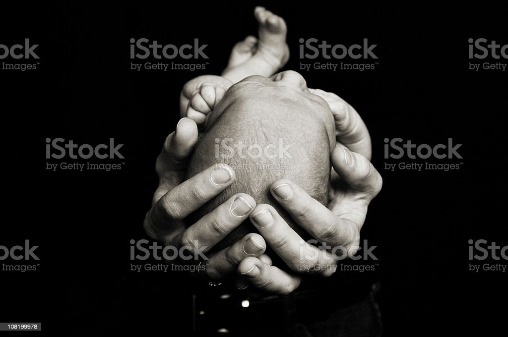 Portrait of Hands Holding Newborn Baby on Black Background stock photo