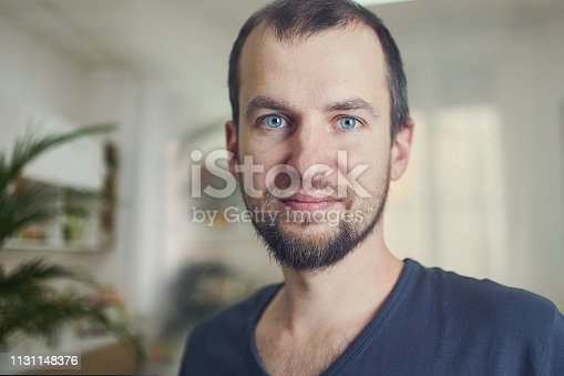Portrait of handsome 35 year old man at home. Blured background