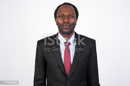 Studio shot of handsome African businessman in suit against white background