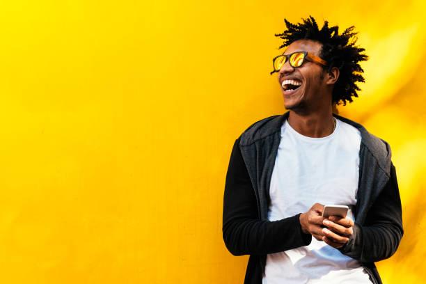 portret przystojnego afro człowieka za pomocą swojego telefonu komórkowego. - kultura młodości zdjęcia i obrazy z banku zdjęć