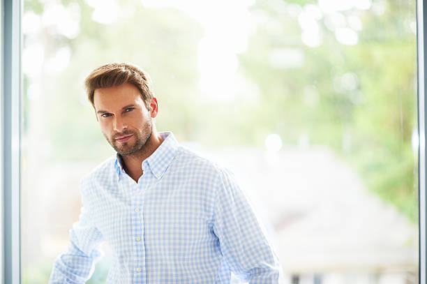 Portrait of handsome and happy man leaning on window stock photo