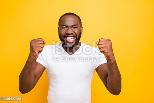 1092211952 istock photo Portrait of handsome attractive manly cheerful glad satisfied mulatto man, showing winning gesture, isolated over bright vivid yellow background 1055427038