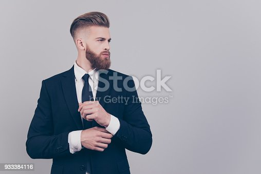 istock Portrait of handsome attractive neat elegant confident serious concentrated rich luxurious virile masculine boss chief fixing cuff-links on sleeve looking aside profile isolated on gray background 933384116