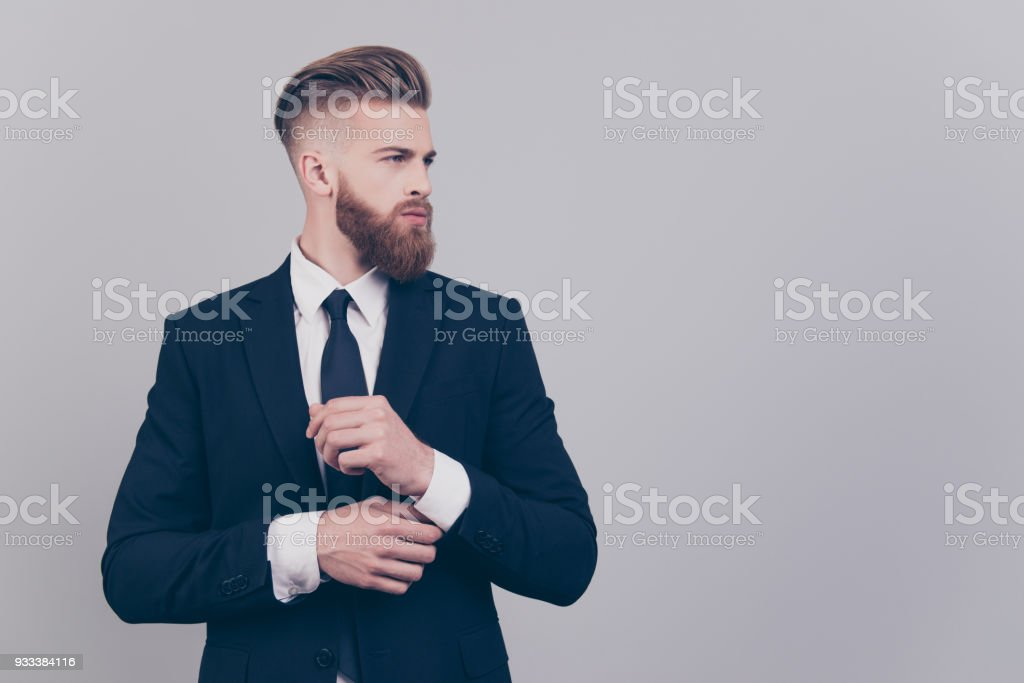 Portrait of handsome attractive neat elegant confident serious concentrated rich luxurious virile masculine boss chief fixing cuff-links on sleeve looking aside profile isolated on gray background stock photo