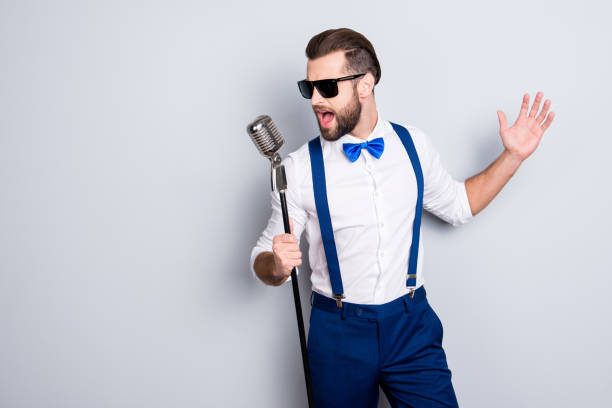 Portrait of handsome attractive singer in blue pants with suspenders and black glasses, singing hit with open mouth in microphone gesture with hand isolated on grey background Portrait of handsome attractive singer in blue pants with suspenders and black glasses, singing hit with open mouth in microphone gesture with hand isolated on grey background singer stock pictures, royalty-free photos & images