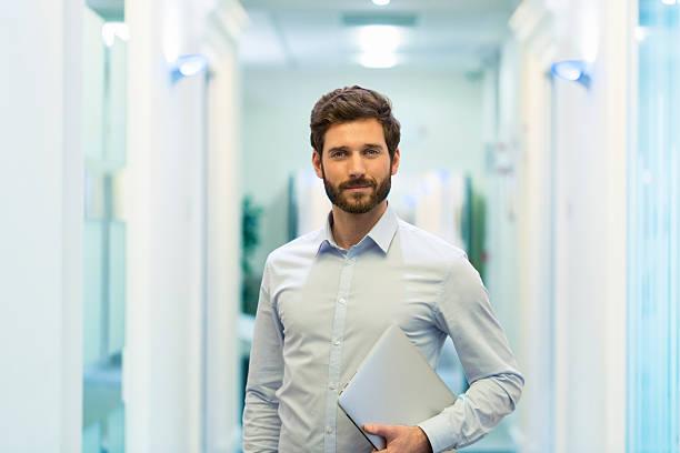 porträt eines gut aussehenden bärtiger mann in business corridor büro - 30 34 jahre stock-fotos und bilder