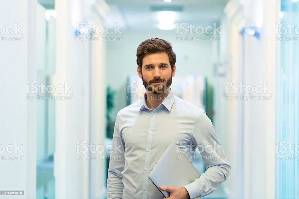 Portrait of handsome bearded business man in corridor office stock photo