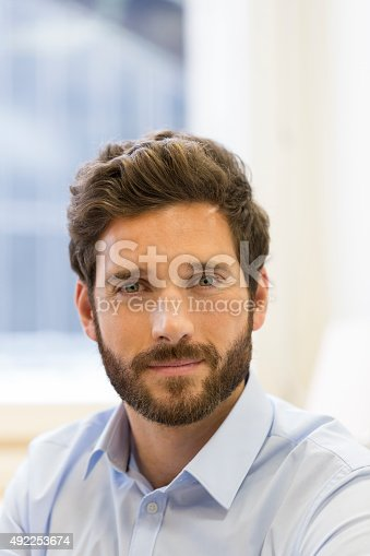 istock Portrait of handsome bearded man in office. looking camera 492253674