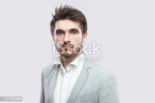 611630440 istock photo Portrait of handsome bearded serious man with brown hairs and beard in white shirt and casual grey suit standing and looking at camera. 1137640869