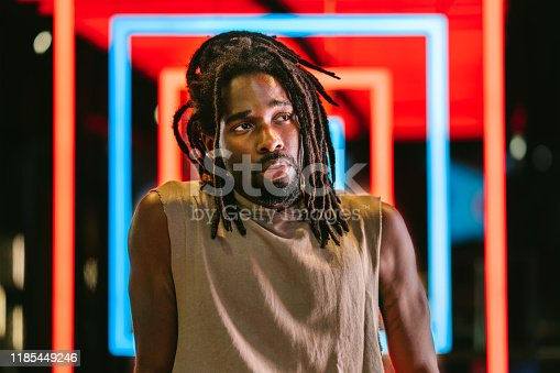 A portrait of a handsome black man in front of colorful neon lights.