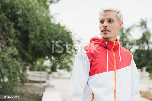 istock Portrait of handsome blond man walking in the park. Young male wearing sportwear outside. Lifestyle, people and travel concept. 951070974