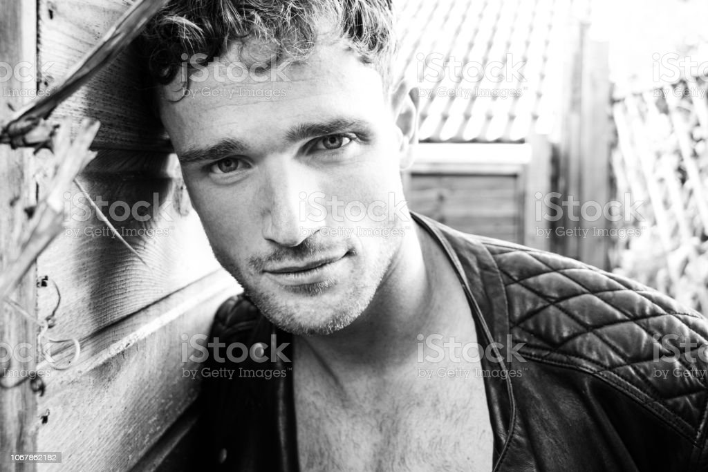 Portrait of handsome blonde man with open leather jacket and stubble looking at camera stock photo
