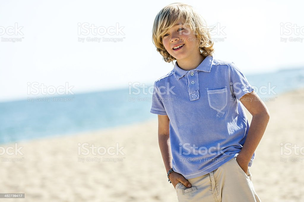 Portrait of handsome boy standing on beach. stock photo