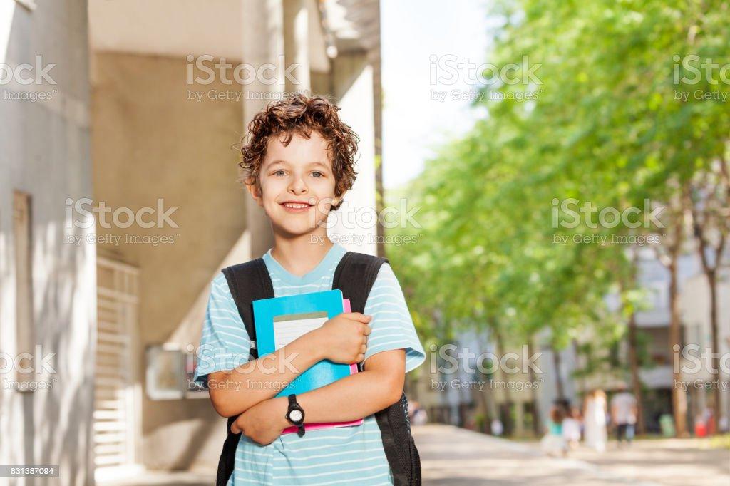 Portret van knappe jongen met boeken in de buurt van school foto