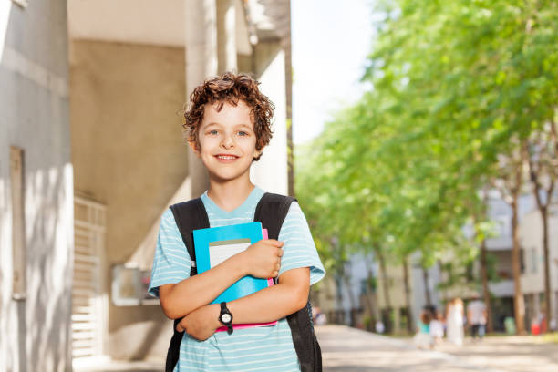 Portrait of handsome boy with books near school stock photo